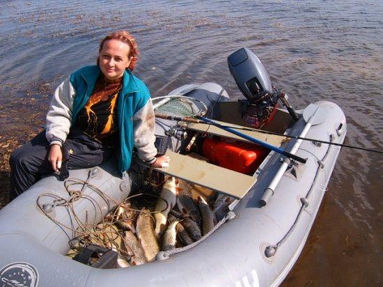 Женщина с уловом в лодке