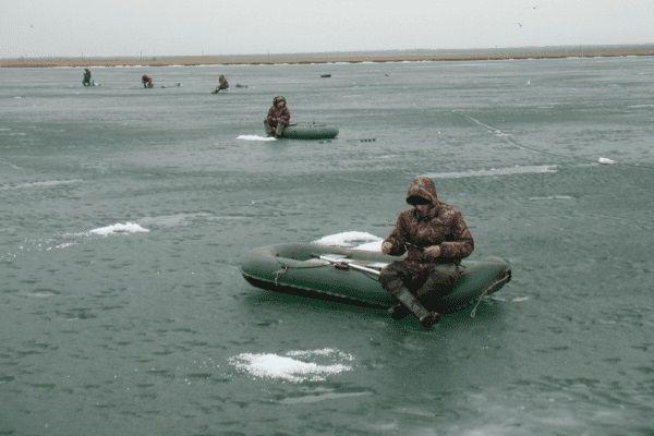 Рыбаки в лодках на льду