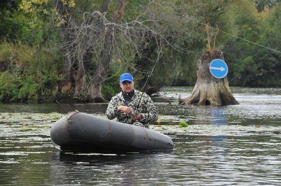 Рыбак в лодке на реке