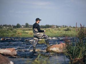 Рыболов в полукомбинезоне на реке
