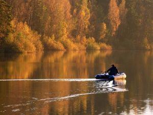 Рыбак в лодке осенью