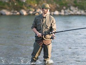 Рыболов в сапогах на реке